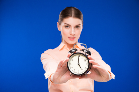 hands  hour: young girl with an alarm clock in focus on a blue background Stock Photo