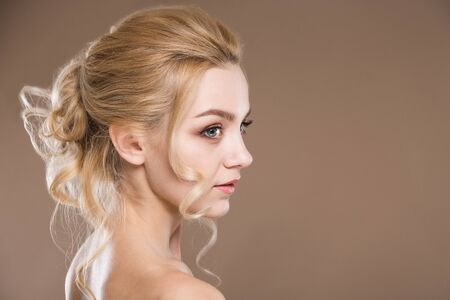 profile of a young blonde woman on a beige background