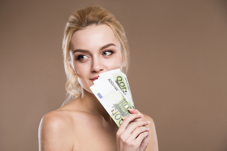 close up portrait of a girl with money near the person with bare shoulders on a beige background