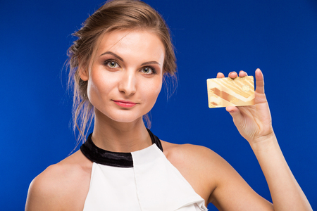 young girl with сredit card in hands on a blue background Stock Photo