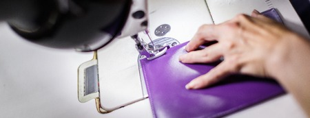 female hands stitching a purple wallet with a sewing machine.