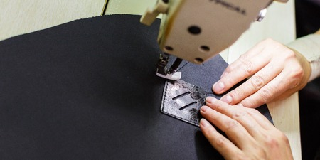close-up of female hands stitching a detail of a bag.