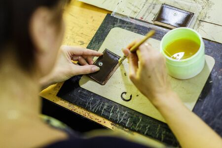 brunette woman smearing with glue a part of a purse with a brush on the wooden table. manufacturing process. close-up photo