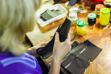 blonde woman in blue unform cutting a part of a wallet with scissors. manufacturing process. jars on the background. close-up photo