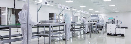 factory workers in white lab suits and face masks, producing tv sets on assebly line with some modern equipment Stock Photo