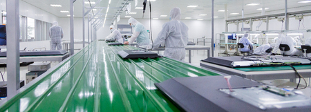 close-up of green assembly line, where factory workers in white lab suits and face masks are producing tv sets with some modern equipment