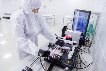 un trabajador de fábrica con traje de laboratorio blanco, guantes de látex y mascarilla, que trabaja con un equipo moderno durante la fabricación de un televisor.
