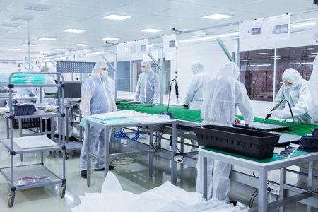 factory workers in white lab suits and face masks, producing tv sets on a green assembly line with some modern equipment Stockfoto