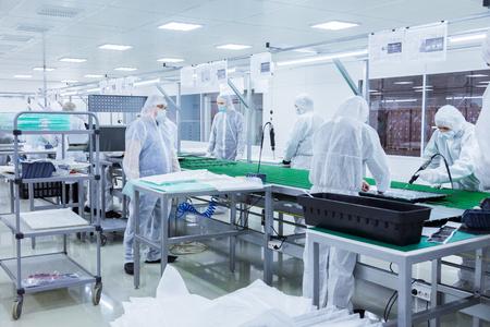 Fabrikarbeiter in weißen Laboranzügen und Gesichtsmasken, die auf einem grünen Fließband mit moderner Ausrüstung Fernseher herstellen Standard-Bild