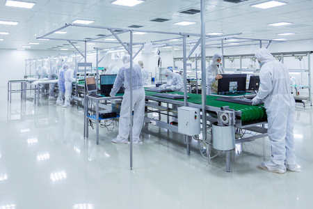 factory workers in white lab suits and face masks, producing tv sets on a green assembly line. some workers are looking into the monitors. Stok Fotoğraf