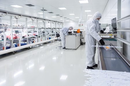 two factory workers in white lab suits and black latex gloves, working with some modern equipment in a very clean room. other workers are on the background. Reklamní fotografie