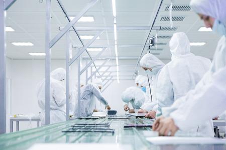 pracownicy fabryki w białych kombinezonach laboratoryjnych i maskach na twarz, produkujący telewizory na zielonej linii montażowej z nowoczesnym wyposażeniem