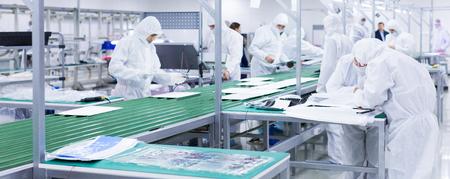 Fabrikarbeiter in weißen Laboranzügen und Gesichtsmasken, die auf einem grünen Fließband mit moderner Ausrüstung Fernseher herstellen