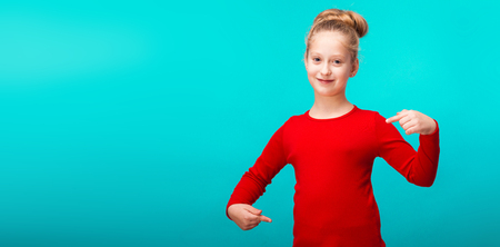 isolated on blue, smiling adorable girl in red pullover with fair-haired updo, pointing at herself and looking into the camera. copyspace.