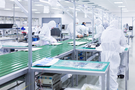 factory workers in white lab suits and face masks, producing tv sets on a green assembly line with some equipment.