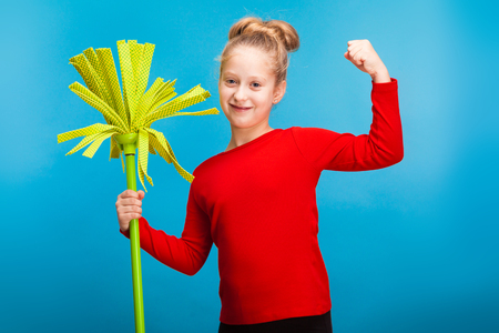 isolated on blue, smiling adorable fair-haired girl in red pullover with a lime green mop, showing her muscles. copyspace. Stock Photo