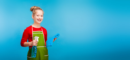 isolated on blue, cute girl in red sweater and olive apron with fair-haired updo, holding a cleanser spray and a blue rag, looking into the camera. copyspace. horizontal picture.