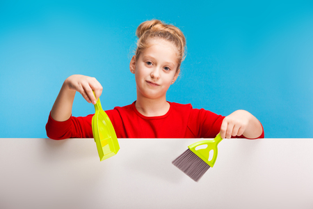 isolated on blue, pretty teenage girl in red sweater with fair-haired updo holding a neon-green scoop and brush in her hands over the white background. copyspace.