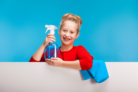 isolated on blue, pretty girl in red sweater with fair-haired updo holding a cleanser sprayer in her hands. a sky-blue rag is lying over the white background. copyspace.