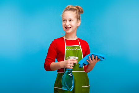 isolated on blue, cute girl in red sweater and olive apron with fair-haired updo, holding a cleanser spray and a blue rag, looking sideways. copyspace.
