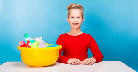 isolated on blue, smiling girl in red pullover with fair-haired updo, sitting at the white table with a lemon washbowl full of multicolored detergents and rags on it. copyspace.