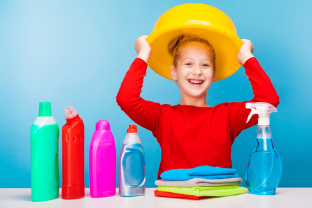 isolated on blue, cheerful girl in red pullover with fair-haired updo, holding a lemon washbowl over her head. multicolored detergents and rags are standing on the table. copyspace.