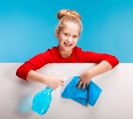 isolated on blue, pretty girl in red sweater with fair-haired updo holding a cleanser sprayer and a sky-blue rag in her hands over the white background. copyspace.