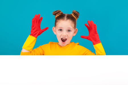 isolated on blue, adorable red-haired girl with freckles in lemon pullover and red latex gloves, shouting and looking into the camera. copyspace. Stock Photo