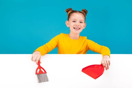 isolated on blue, smiling teenage girl in lemon sweater with red-haired updo holding a scarlet scoop and brush in her hands over the white background. copyspace.