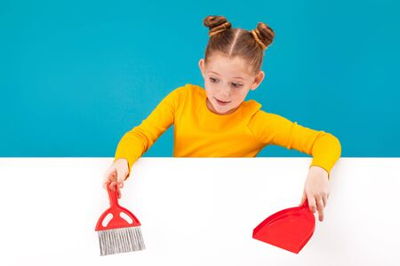isolated on blue, adorable teenage girl in lemon sweater with red-haired updo holding a scarlet scoop and brush in her hands over the white background. copyspace.