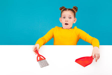 isolated on blue, pop-eyed teenage girl in lemon sweater with red-haired updo holding a scarlet scoop and brush in her hands over the white background. copyspace. Stock Photo