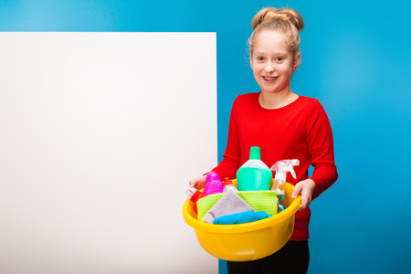 isolated on blue and white, smiling girl in red pullover and black trousers with fair-haired updo, holding a lemon washbowl with multicolored detergents and rags. copyspace.
