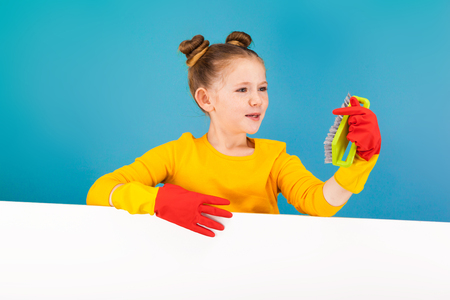 isolated on blue, adorable red-haired girl with freckles in lemon pullover and red latex gloves, holding a lime brush and looking at it. copyspace.