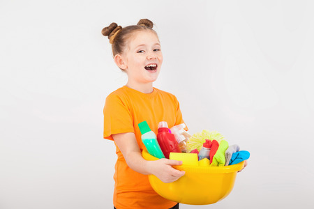 isolated on white, happy red-haired girl with freckles in tangerine T-shirt and black trousers, holding a lemon washbowl with multicolored detergents,rags and sponges. copyspace.