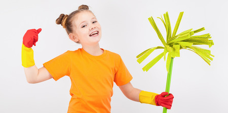 isolated on white, smiling red-haired girl with freckles in orange T-shirt and red latex gloves, holding a lime green mop and showing her muscles. copyspace. Stock Photo