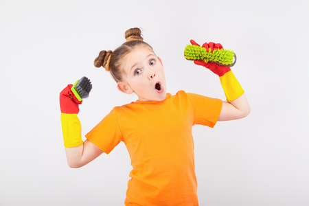 isolated on white, adorable red-haired girl with freckles in orange T-shirt and red latex gloves, holding green brushes in her hands and making faces. copyspace. Stock Photo