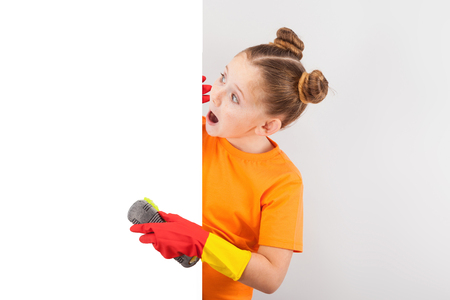 isolated on white, surprised red-haired girl with freckles in orange T-shirt and red latex gloves, polishing the white background with a grey-green brush. copyspace.