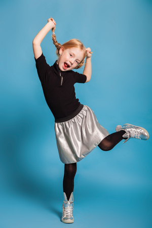 isolated on blue, red-haired girl in black sweater with zipper, black tights, silver skirt and sneakers, making faces and holding her braids up. copyspace.