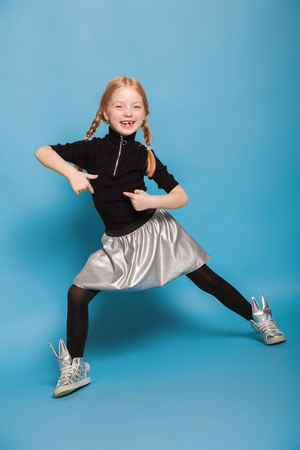 isolated on blue, smiling red-haired girl with braids in black sweater with zipper, black tights, silver skirt and sneakers, pointing at herself. feet are widely apart.copyspace. Stock Photo