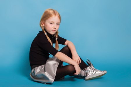 isolated on blue, adorable red-haired girl with braids in black sweater with zipper, black tights, silver skirt and sneakers, sitting and looking into the camera. copyspace.