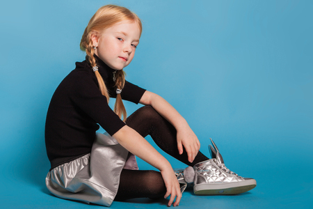 isolated on blue, red-haired girl with braids in black sweater with zipper, black tights, silver skirt and sneakers, sitting and looking arrogantly into the camera. copyspace.