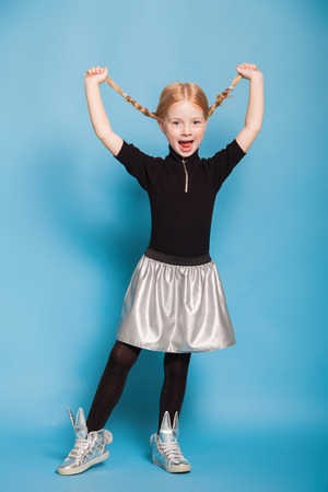 isolated on blue, red-haired girl in black sweater with zipper, black tights, silver skirt and sneakers, holding her braids up and shouting. copyspace. Stock Photo