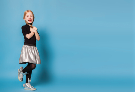 isolated on blue, red-haired girl in black sweater with zipper, black tights, silver skirt and sneakers, holding her hands and braids crossed. open mouth with missing teeth. copyspace. Stock Photo