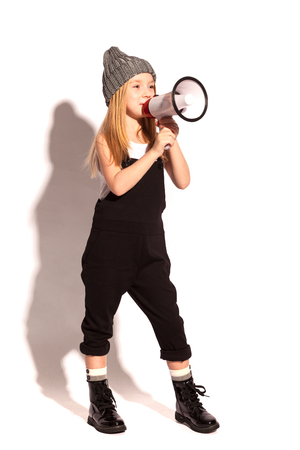 isolated on white, cheerful red-haired girl without a tooth in black overalls, white t-shirt, grey hat and lacquered lace-up shoes, speaking into the megaphone. copyspace. Foto de archivo