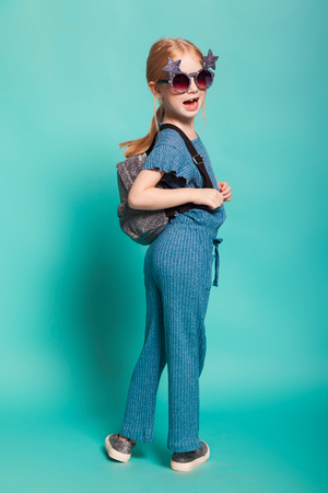 isolated on blue, happy red-haired girl in star-shaped sunglasses, blue overall and silver slip ons, holding a lustrous backpack. copyspace.