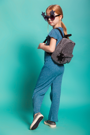 isolated on blue, red-haired girl in star-shaped sunglasses, blue overall and silver slip ons, holding a lustrous backpack and posing at studio. copyspace.