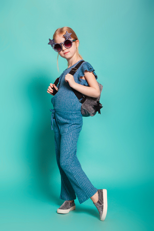isolated on blue, red-haired girl in star-shaped sunglasses, blue overall and silver slip ons, holding a lustrous backpack. copyspace.