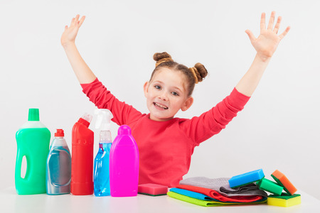 isolated on white, smiling red-haired girl in rose sweater holding her hands up. multicolored detergents, rags and sponges are on the white table. copyspace. Stock Photo