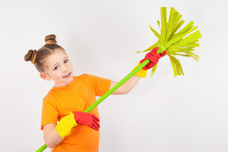 isolated on white, adorable red-haired girl with freckles in orange T-shirt and red latex gloves, holding a lime green mop. copyspace.