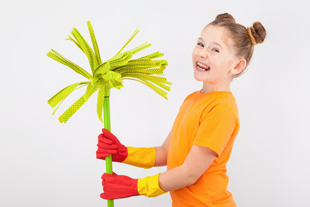 isolated on white, super happy red-haired girl with freckles in orange T-shirt and red latex gloves, holding a lime green mop. copyspace. Stock Photo